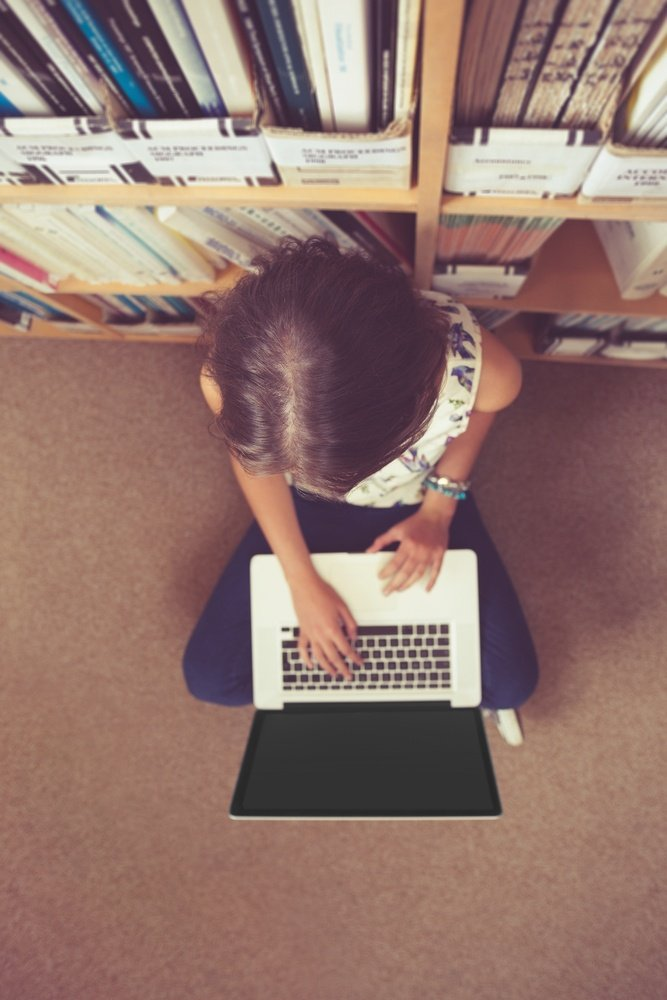 High angle view of a female student sitting against bookshelf and using laptop on the library floor.jpeg